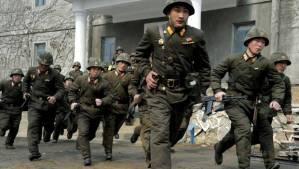 North Korean troops running through a South Korean town.